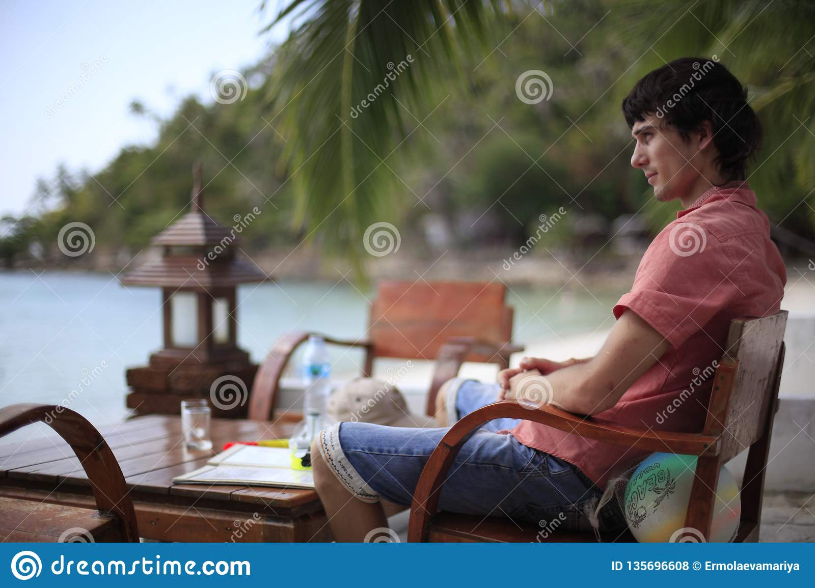 Handsome Young Man In Sits In Beach Cafe By Sea Has Vacation Time Travel Concept Stock Photo Image Of Enjoying Morning 135696608