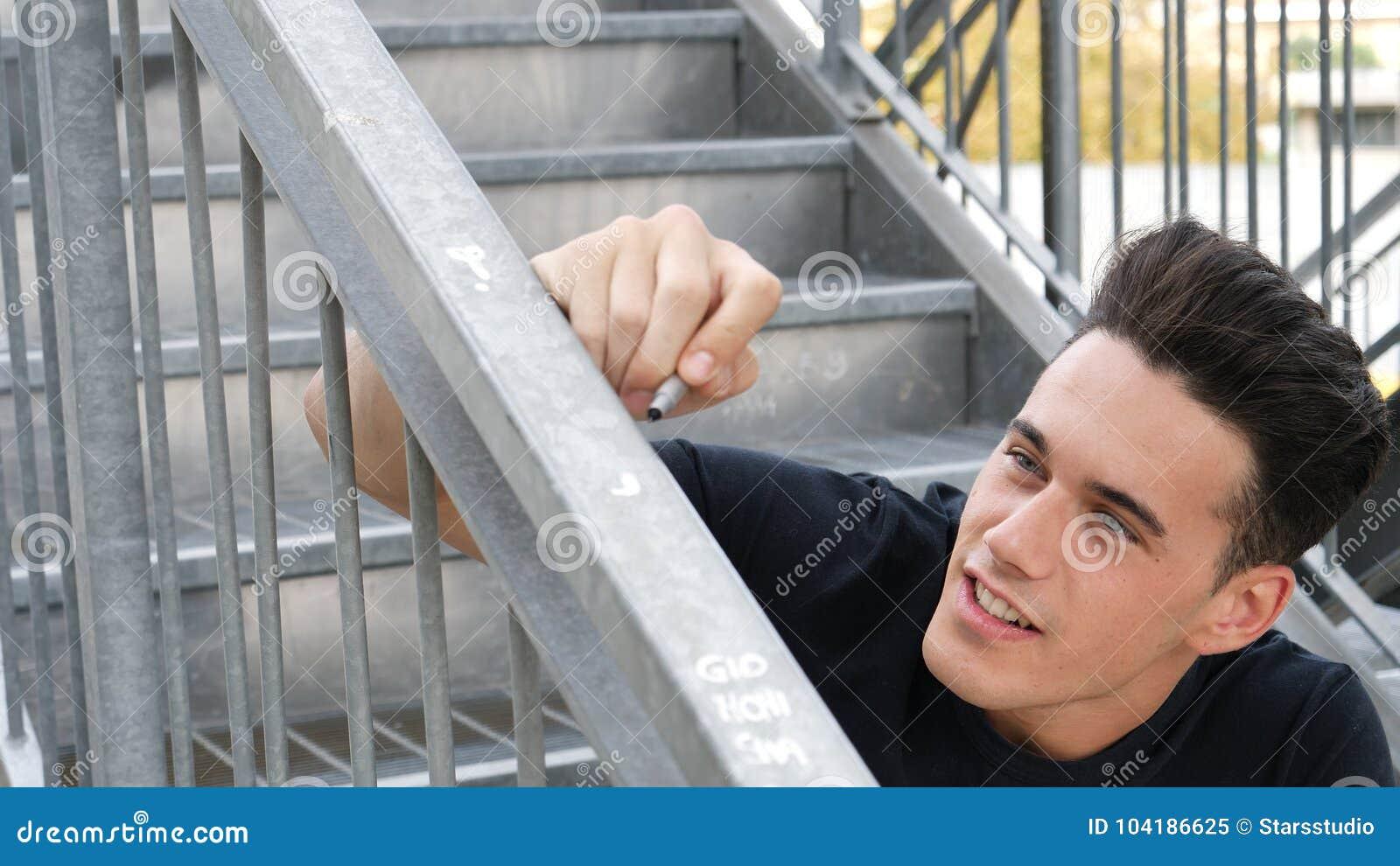 Man writing on banister or handrail