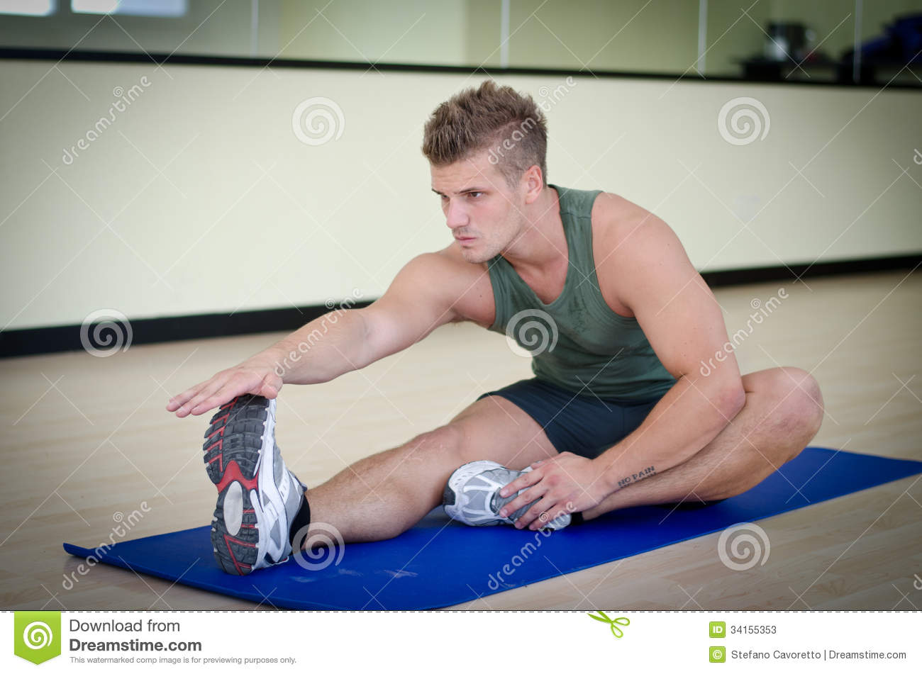 Handsome Young Man Stretching On Gym Mat Stock Photos