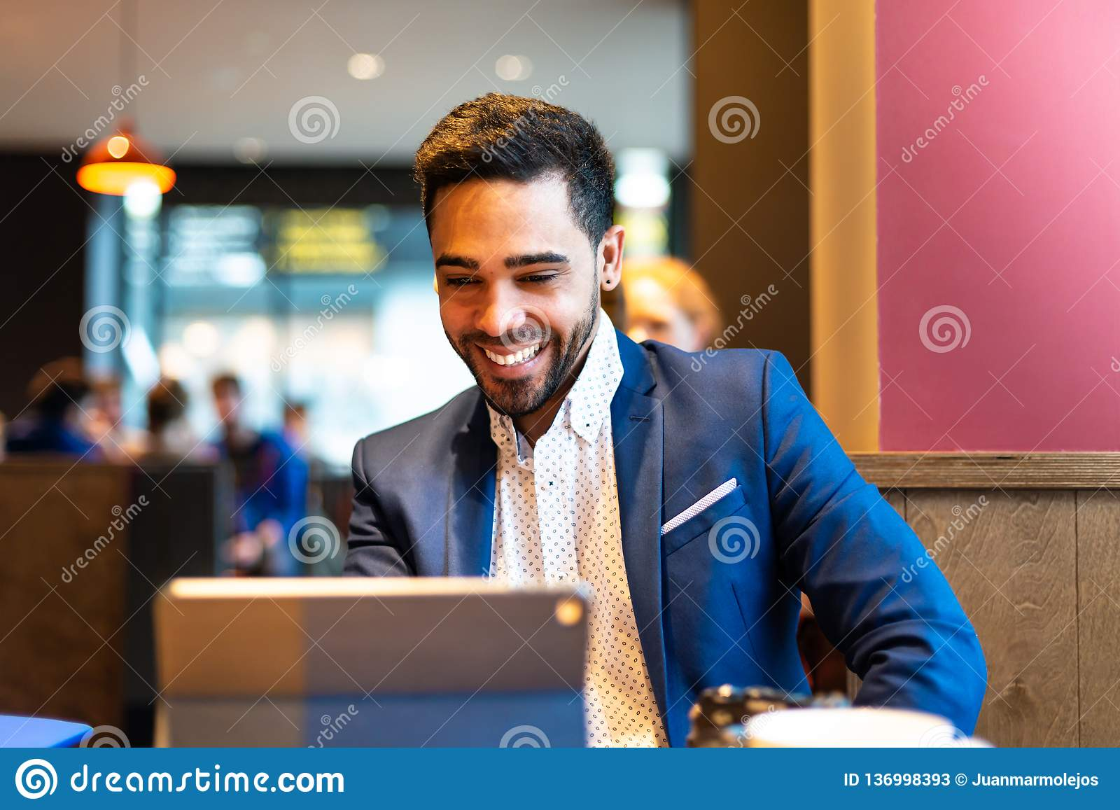 Handsome young man on suit using laptop