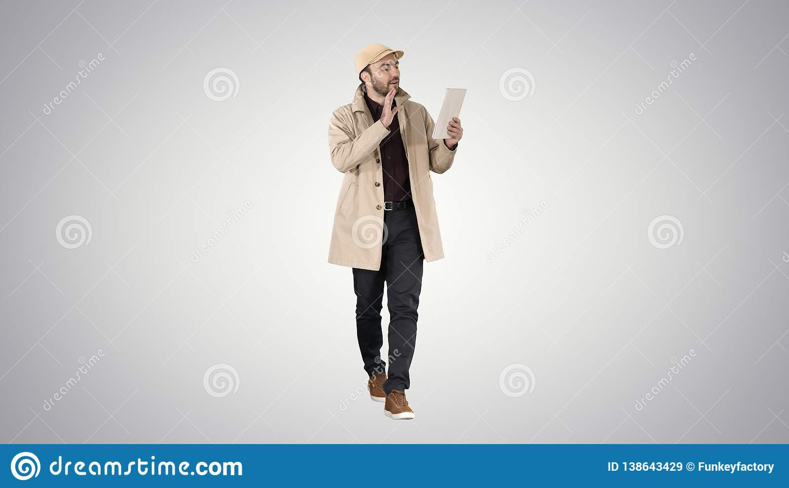 Handsome young man with tablet making video call on gradient background.