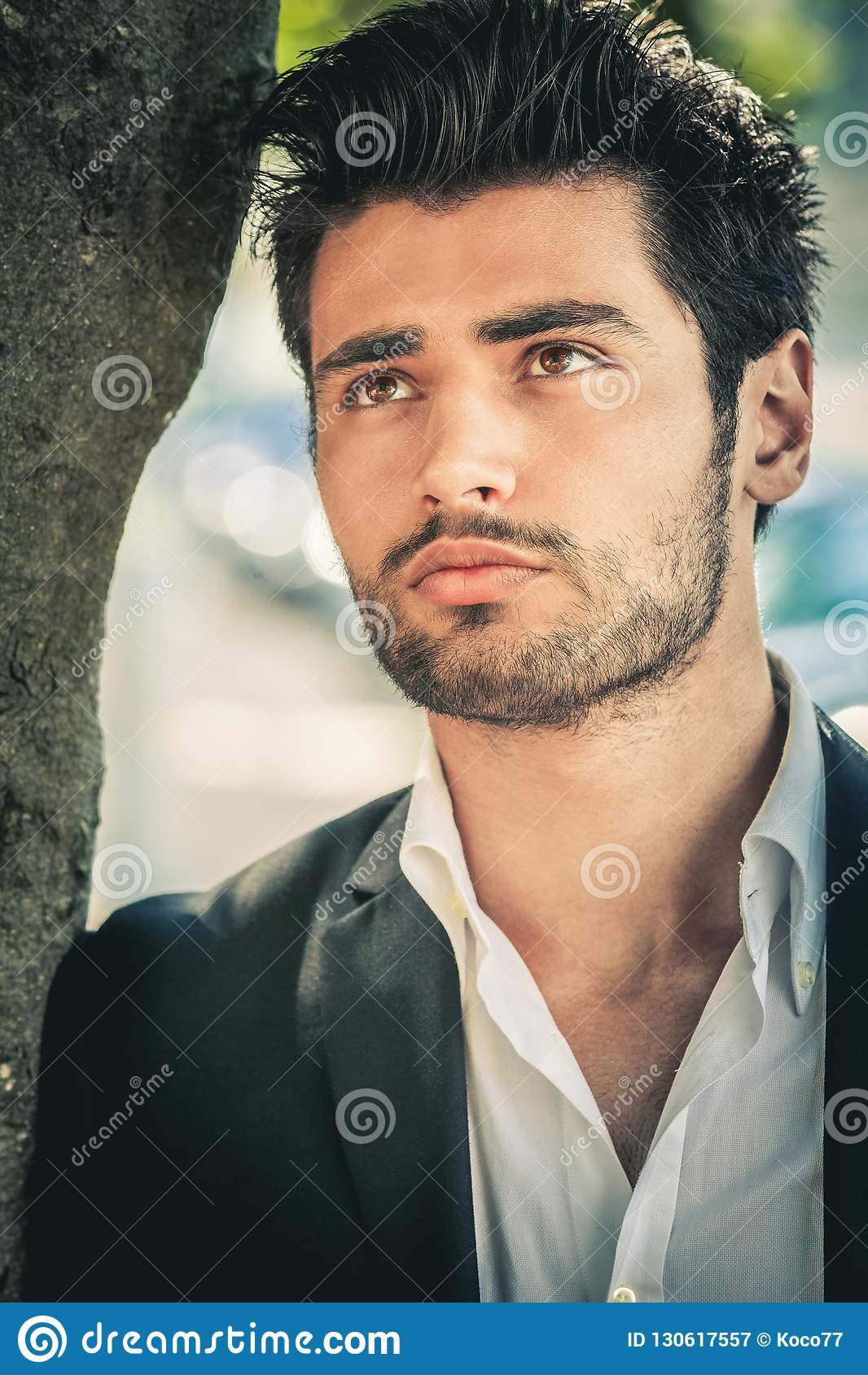 Handsome young man thinking. Outdoors, near a tree.
