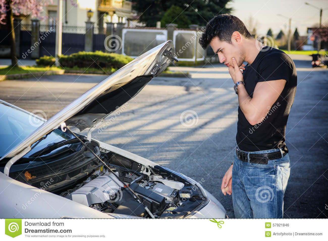 Handsome young man trying to repair a car engine stock Auto motor repair