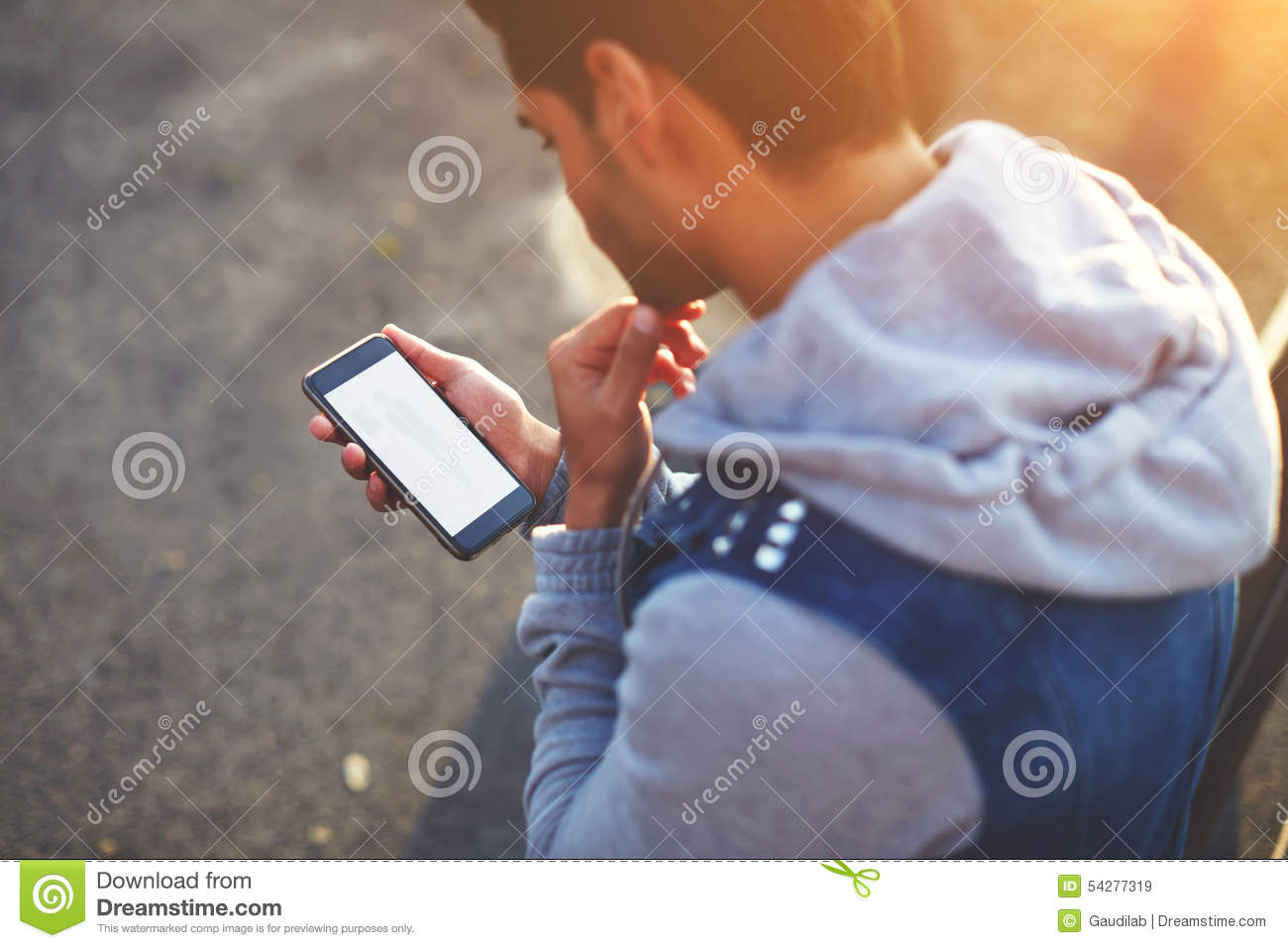 Handsome young man using smart phone while standing outdoors at sunny evening