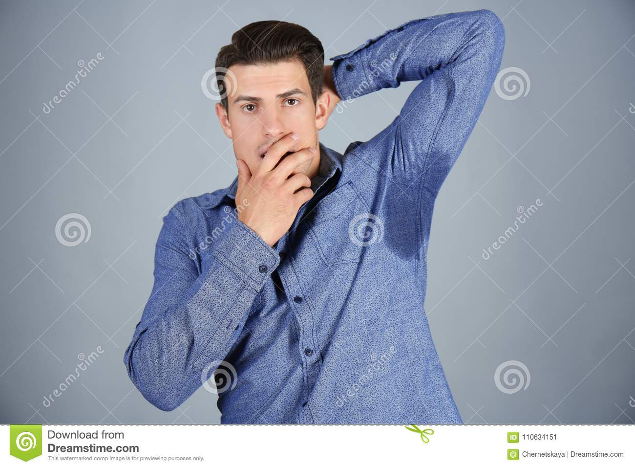 Handsome young man with wet spot on clothes under armpit against grey background.