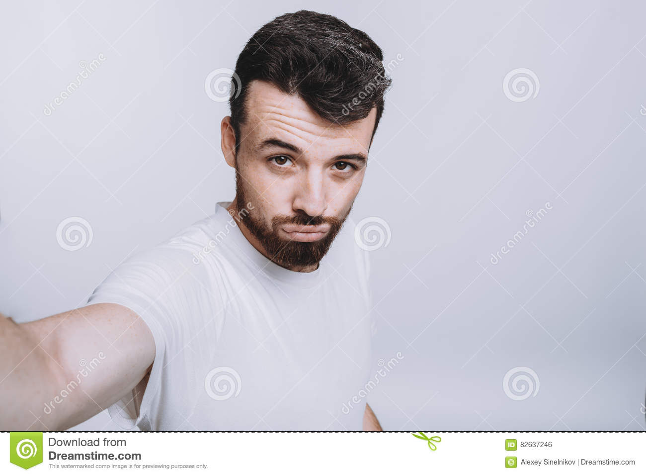 Handsome young man in white shirt doing selfie