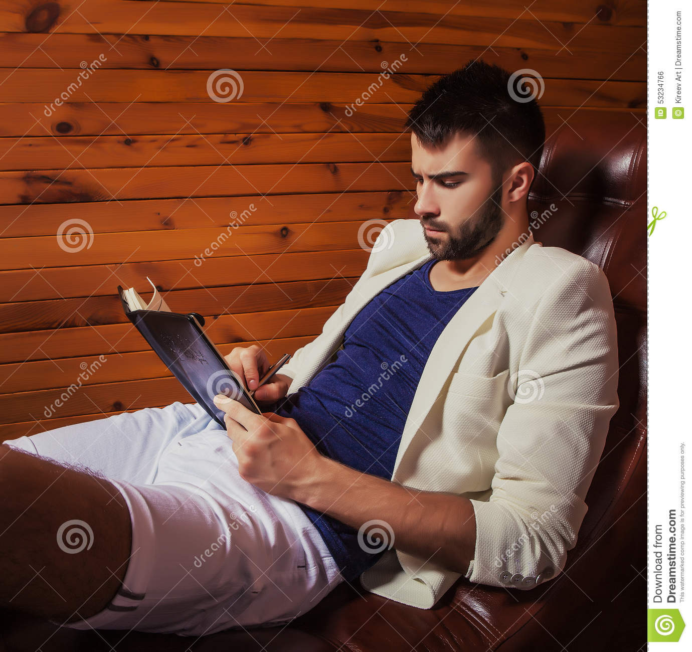 Handsome young man in white suit relaxing on luxury sofa with diary.