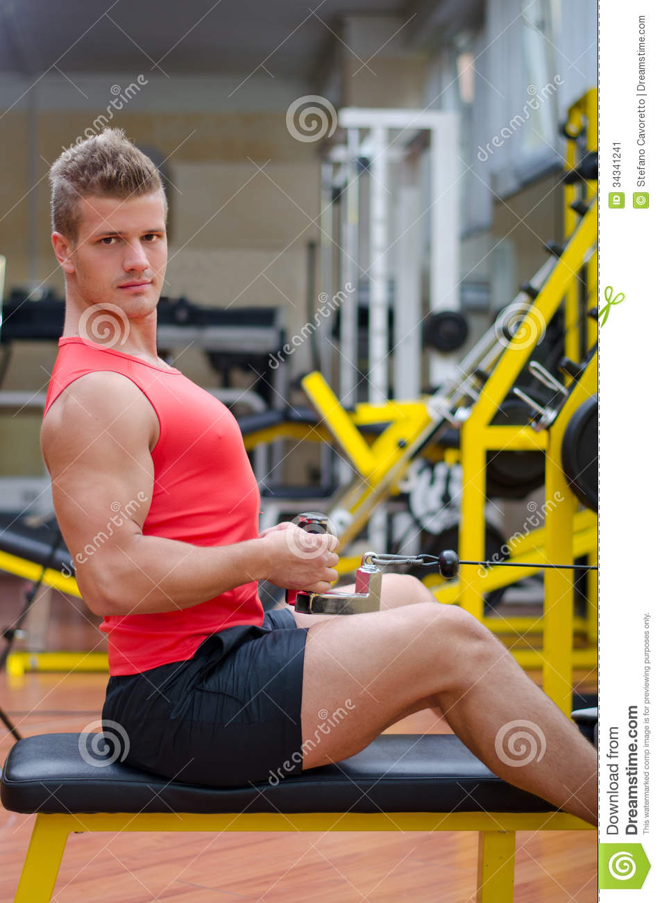 Handsome Young Man Working Out On Gym Equipment Stock ...