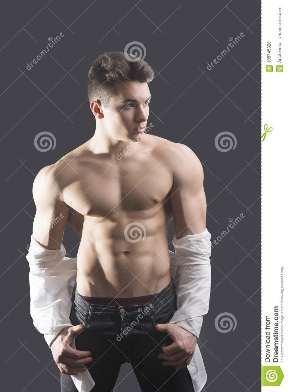 American Gladiators Naked young muscleman undressing on dark background stock photo