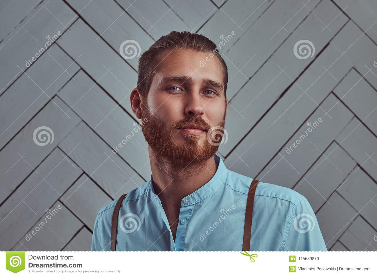 Handsome young retro stylish redhead man in suspenders posing against a white wall in a studio.