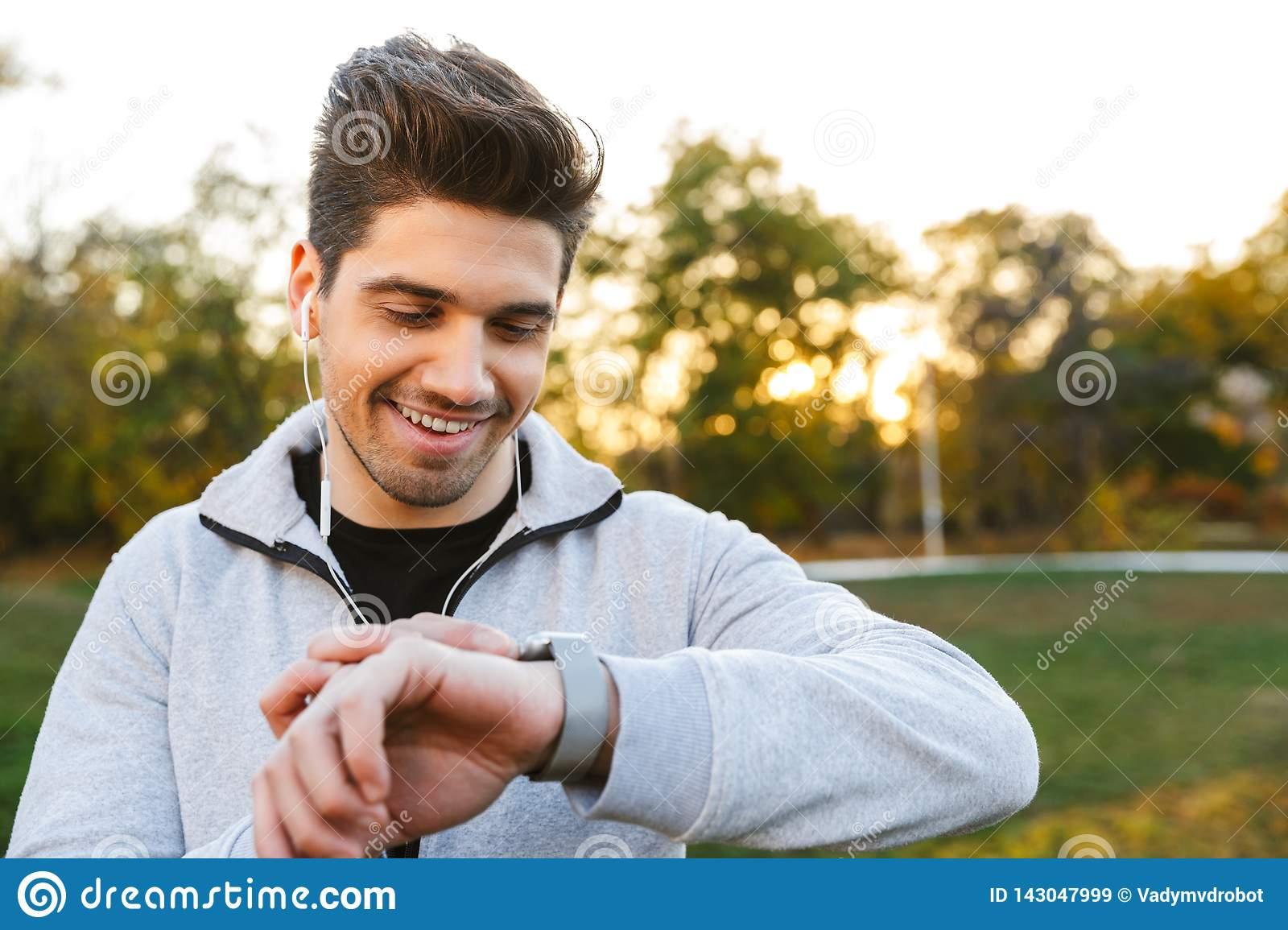 Handsome young sportsman outdoors in park listening music with earphones looking at watch