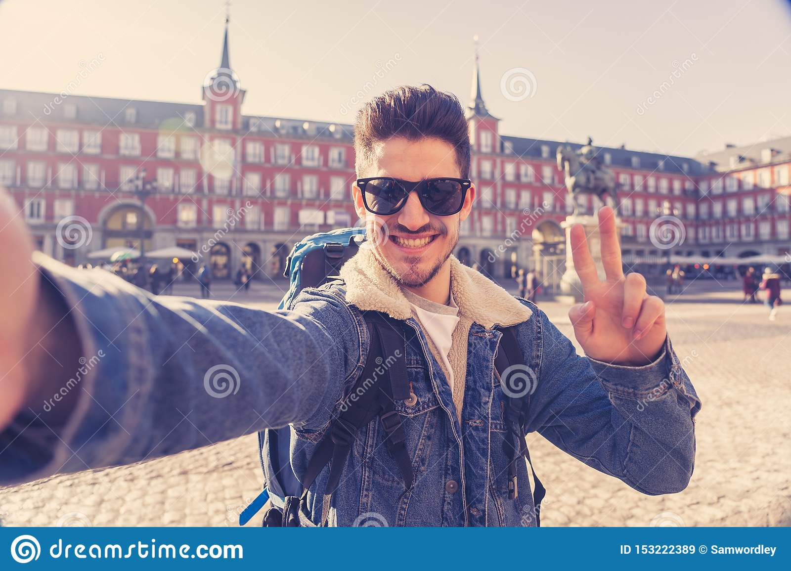 Handsome young student tourist man happy and excited taking a selfie in Madrid, Spain