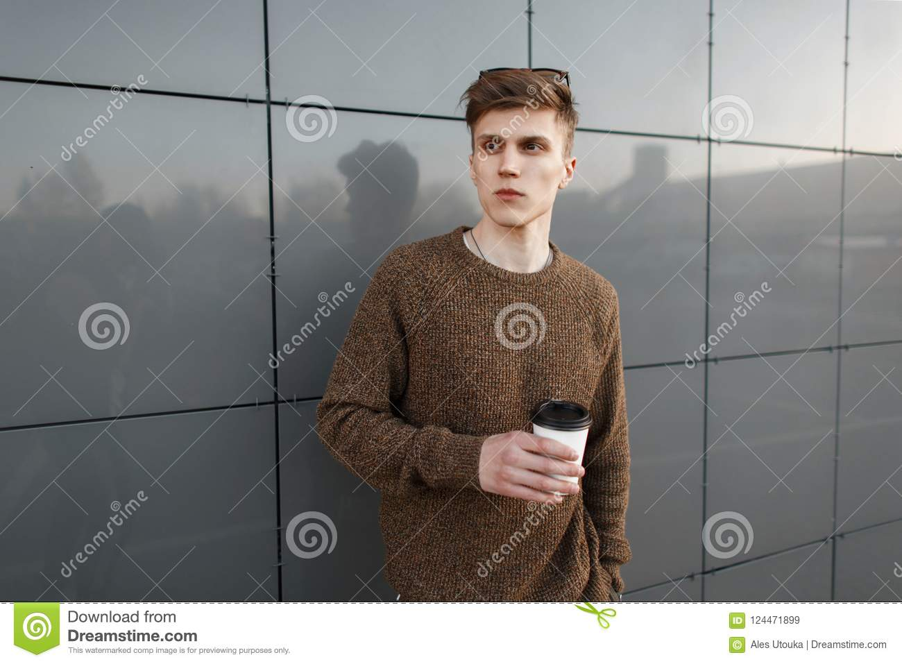 3e94635dbc4 Handsome young stylish man with a hairstyle in a fashion pullover holding a  cup of coffee on the street