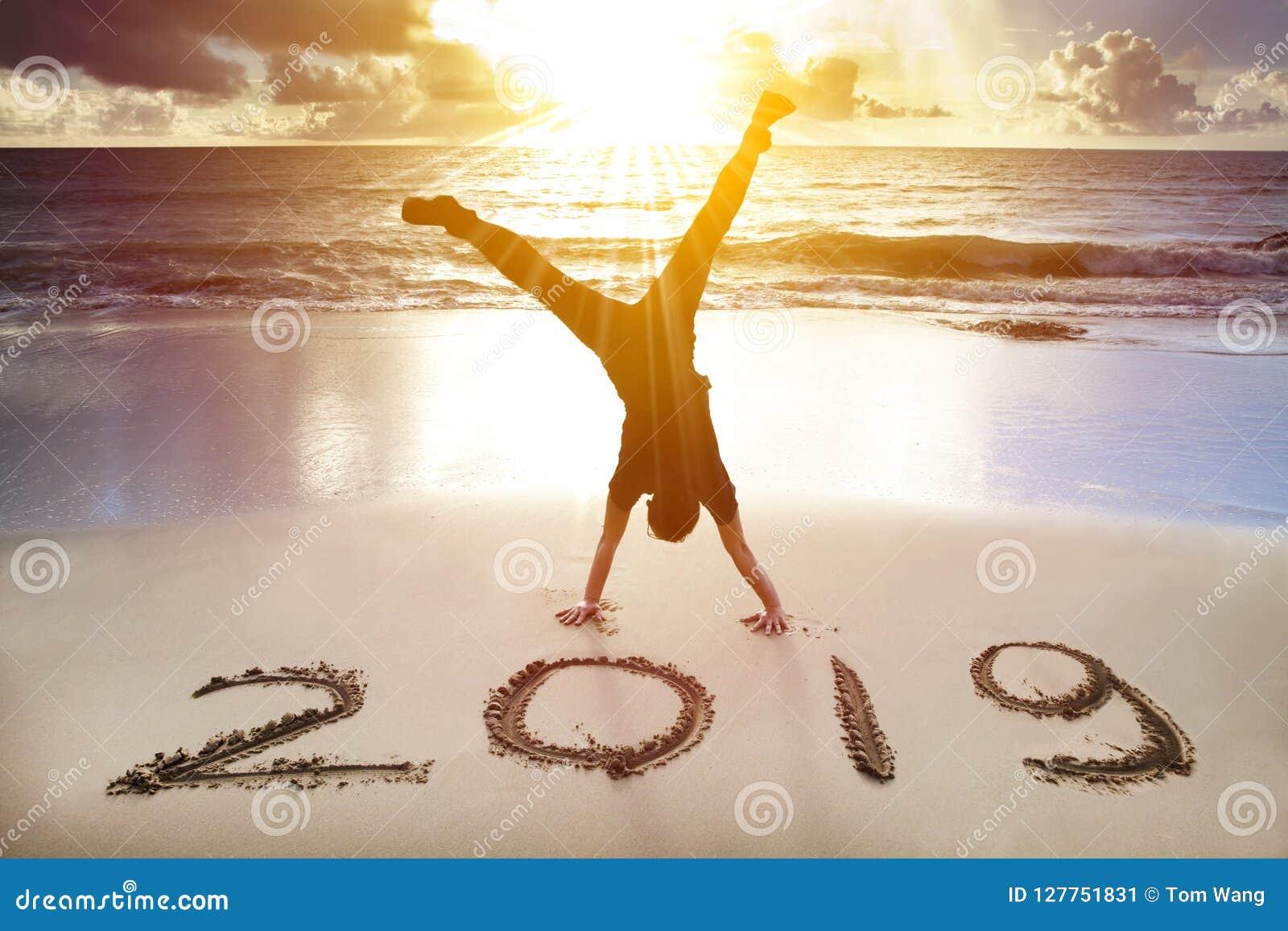 Handstand человека на пляже Счастливая концепция 2019 Нового Года