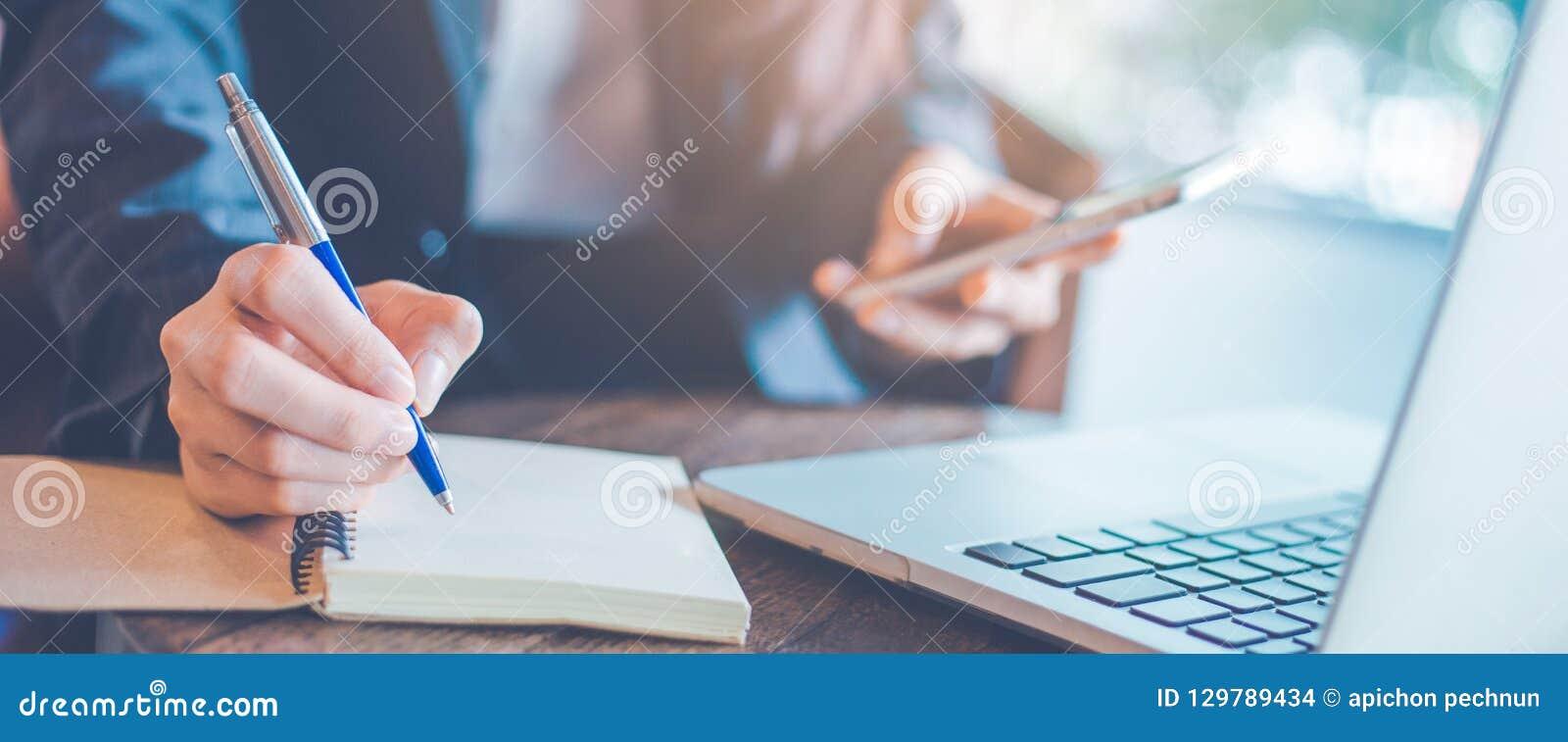 Handstil för hand för affärskvinna på en notepad med en penna i offien