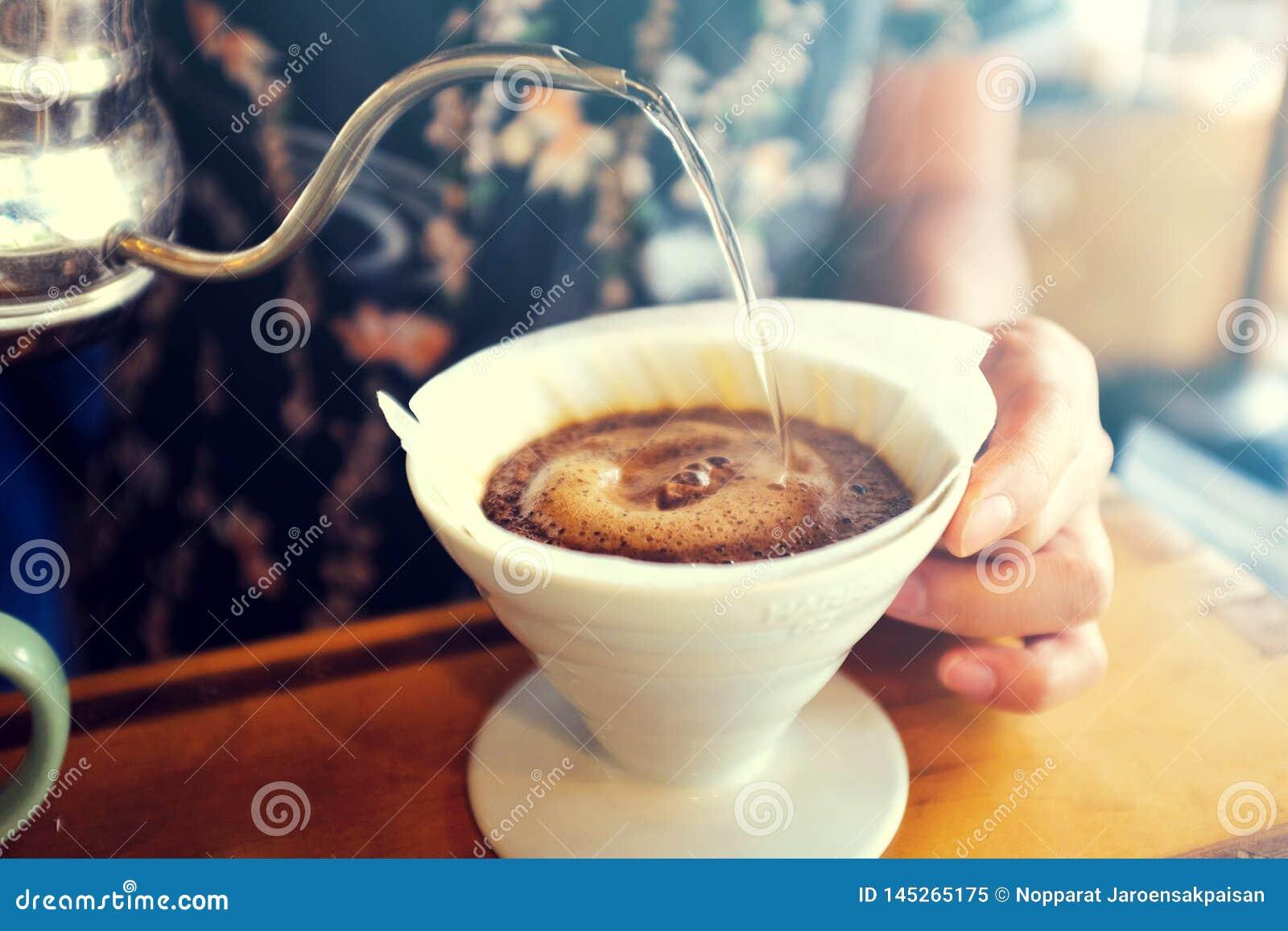 Handtropfenfänger-Kaffee, Barista, das Heißwasser auf gebratenem Kaffeesatz gießt