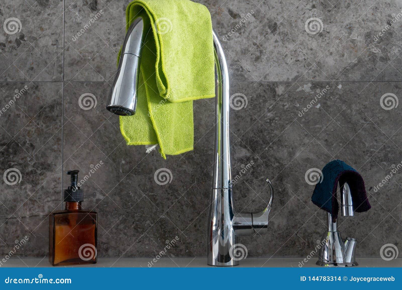 Handtvålpump, kromdiskhovattenkran, filtrerat vattenklapp med microfibretorkdukar och grå backsplash för marmorstentegelplatta