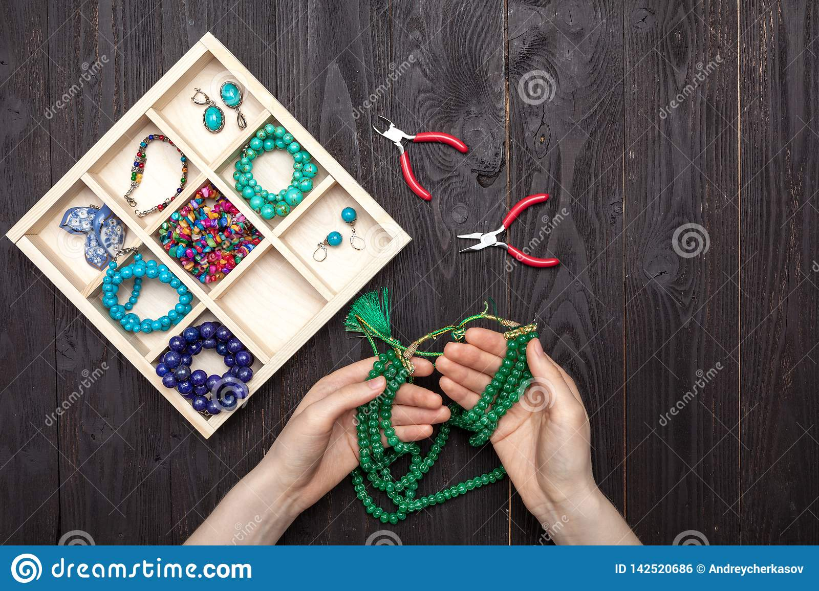 Handwork at home, the girl makes jewelry hands on the table