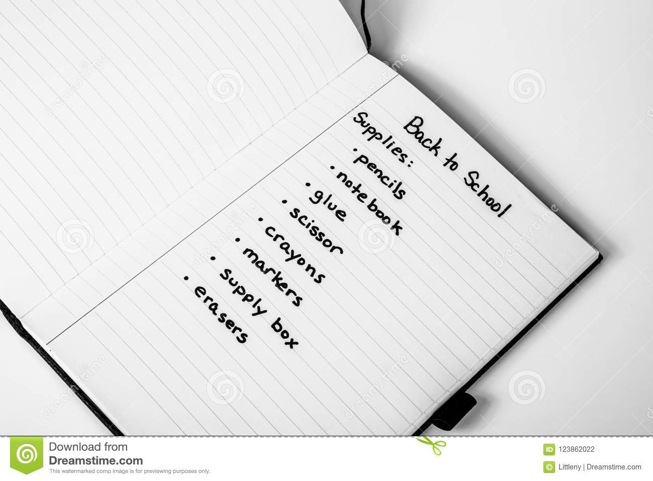 handwritten shopping list of back to school supplies stock photo