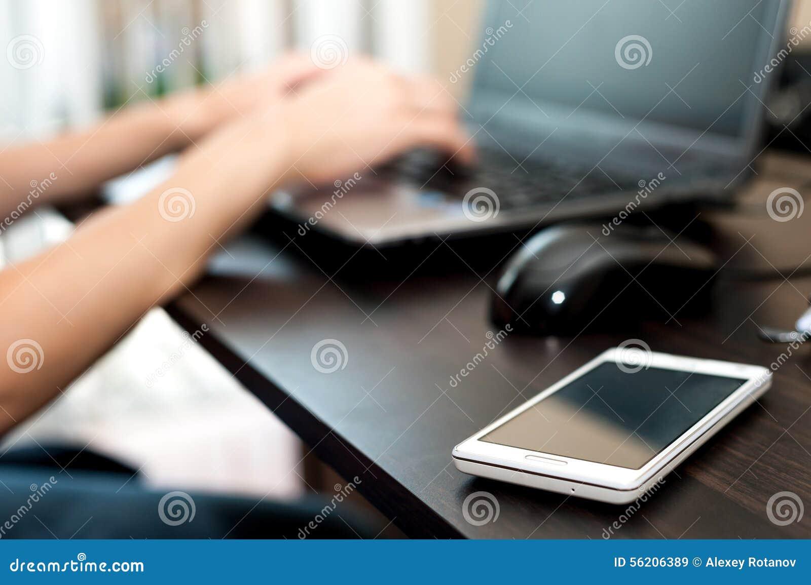 Handy (Smartphone) auf einer Tabelle und einer Frau, die an der Laptop-Computer arbeiten