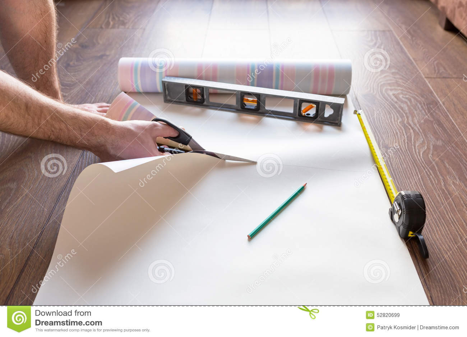 Handyman cutting wallpaper