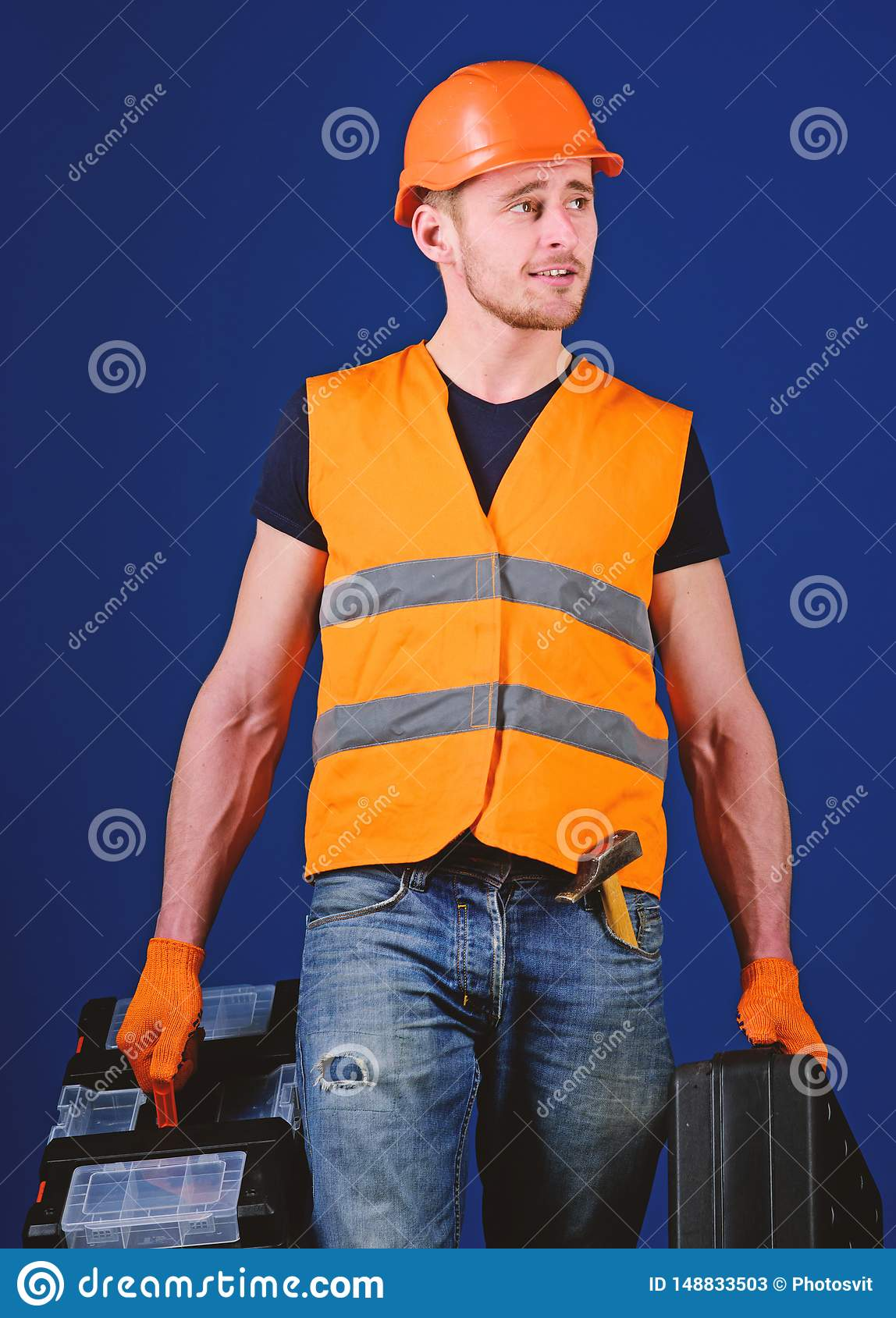 Handyman, repairman on dreamy face goes and carries bags with professional equipment. Man in helmet, hard hat holds