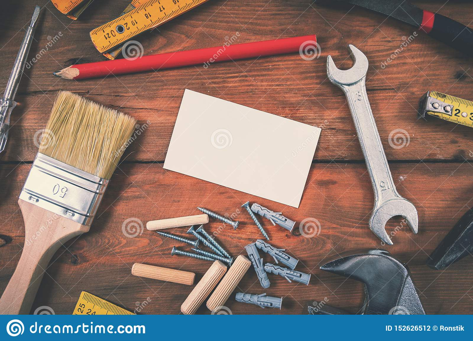 Handyman services home repair - blank business card with construction tools on wooden background