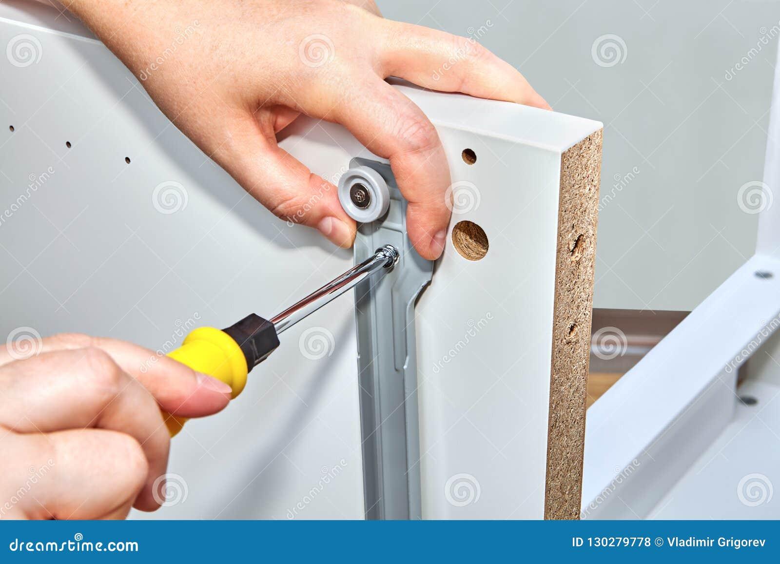 Handyman Tightens Bolt Fixings In Drawer Slide Brackets Stock Photo