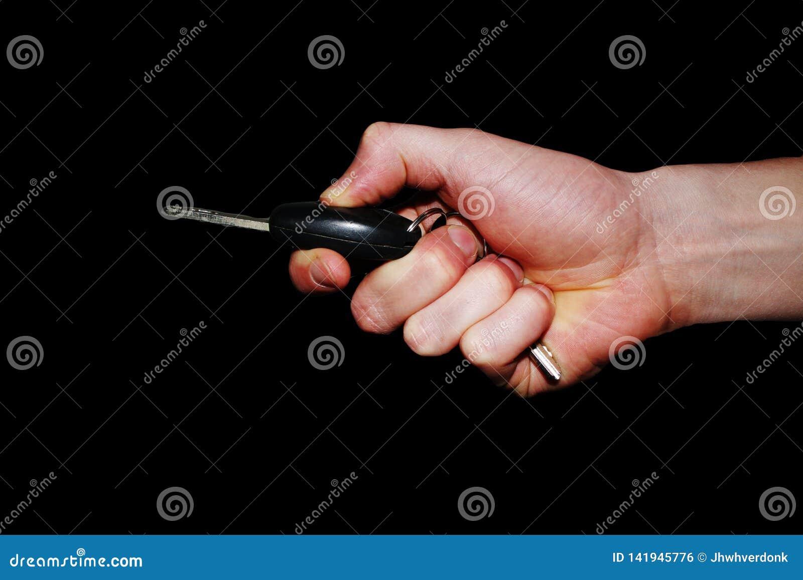 Handzeichen - Hand, die einen Autoschlüssel hält und den Knopf drückt, um ihn zu öffnen