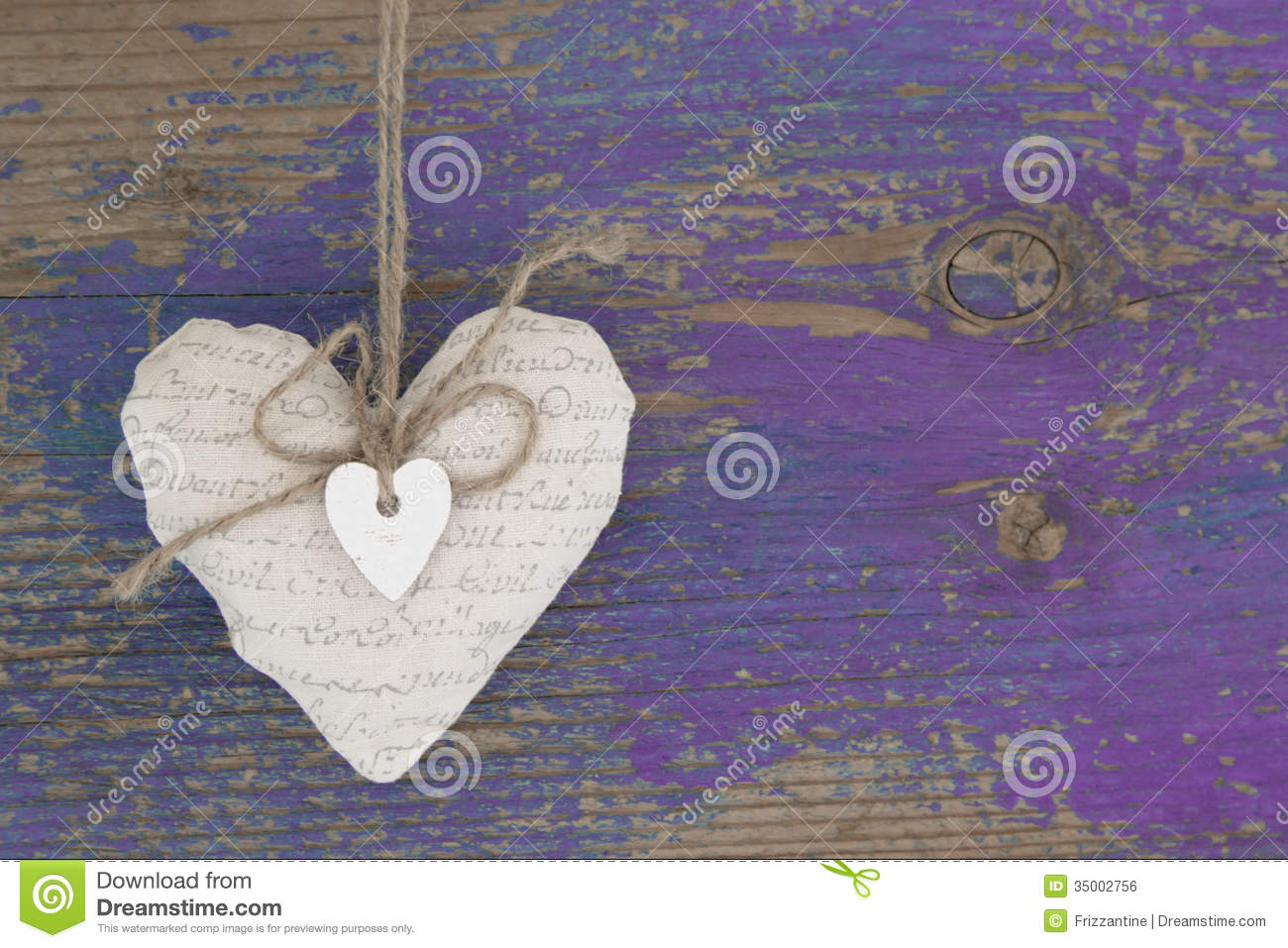 Hanging heart and purple wooden background in country style.