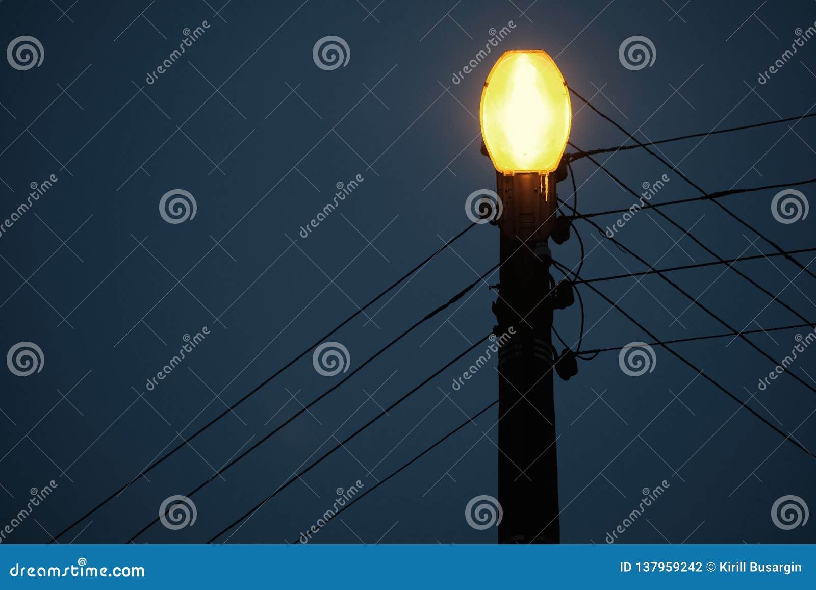 A hanging street lamp against a serene dark sky