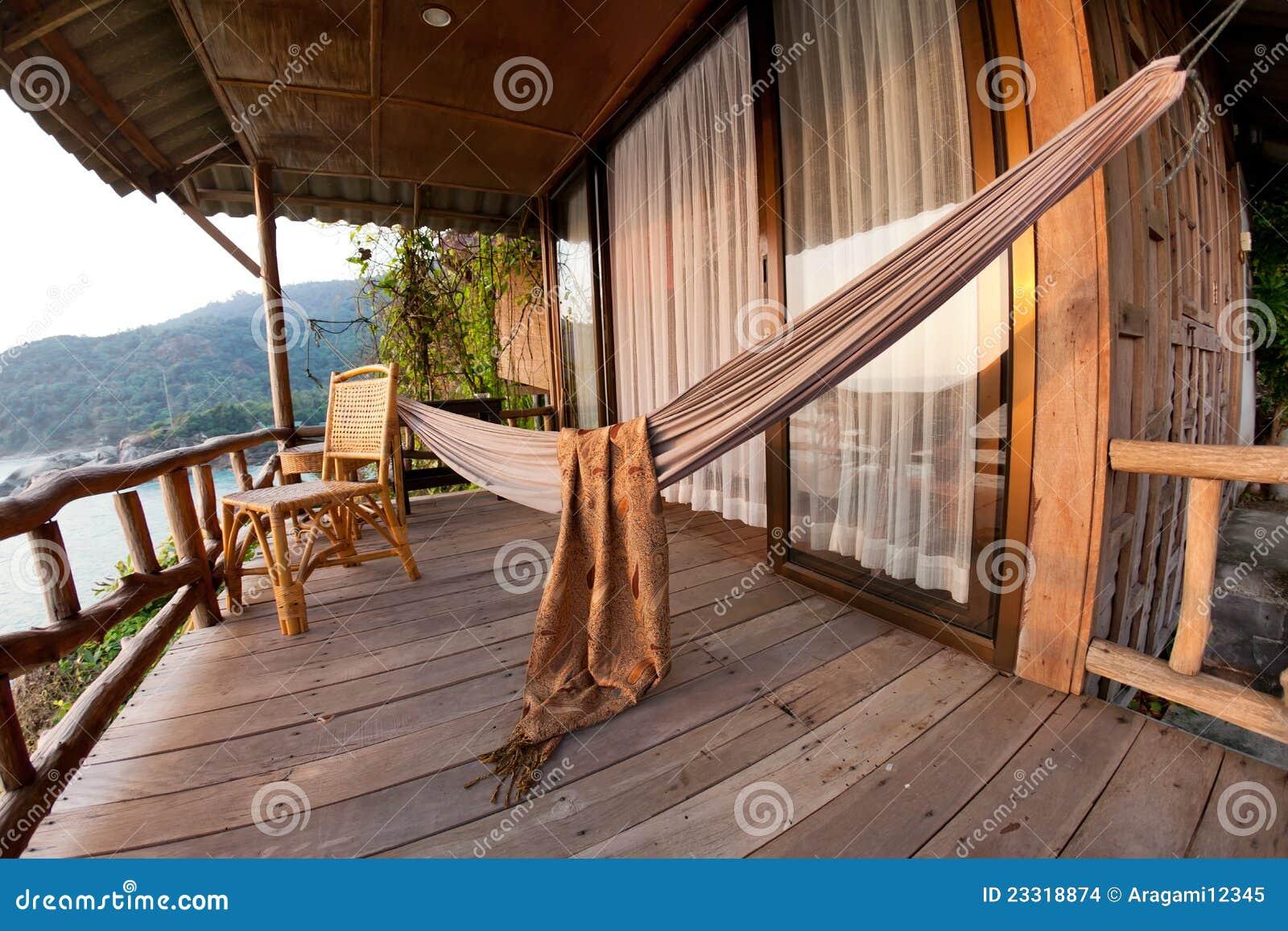 Hangmat en stoel op terras van bungalow stock foto afbeelding