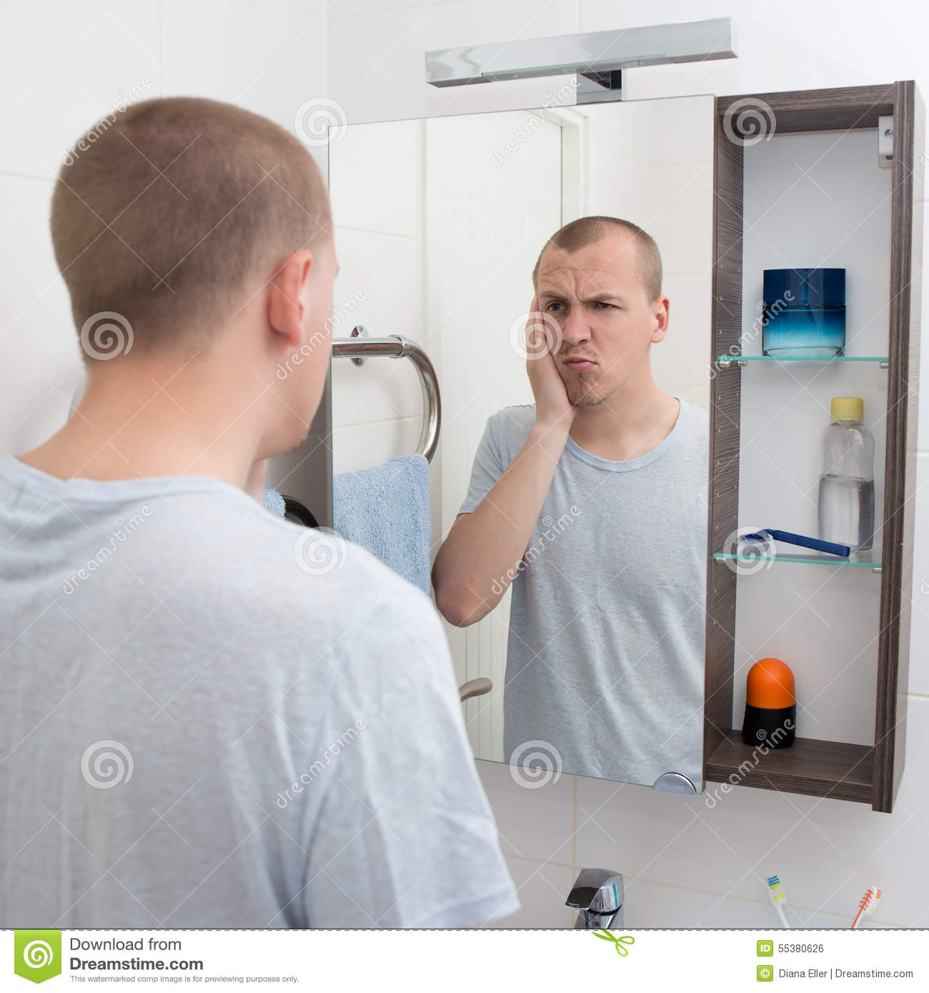 Hangover concept tired man looking at mirror in bathroom for Looking mirror