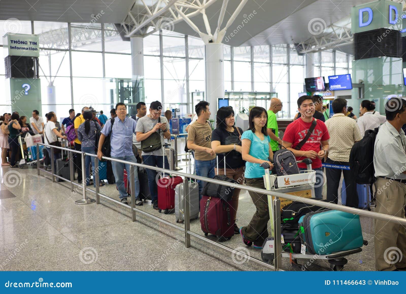 Hanoi, Vietnam - 29 aprile 2016: Coda della gente asiatica nella linea che aspetta al portone di imbarco nell aeroporto di Noi Ba