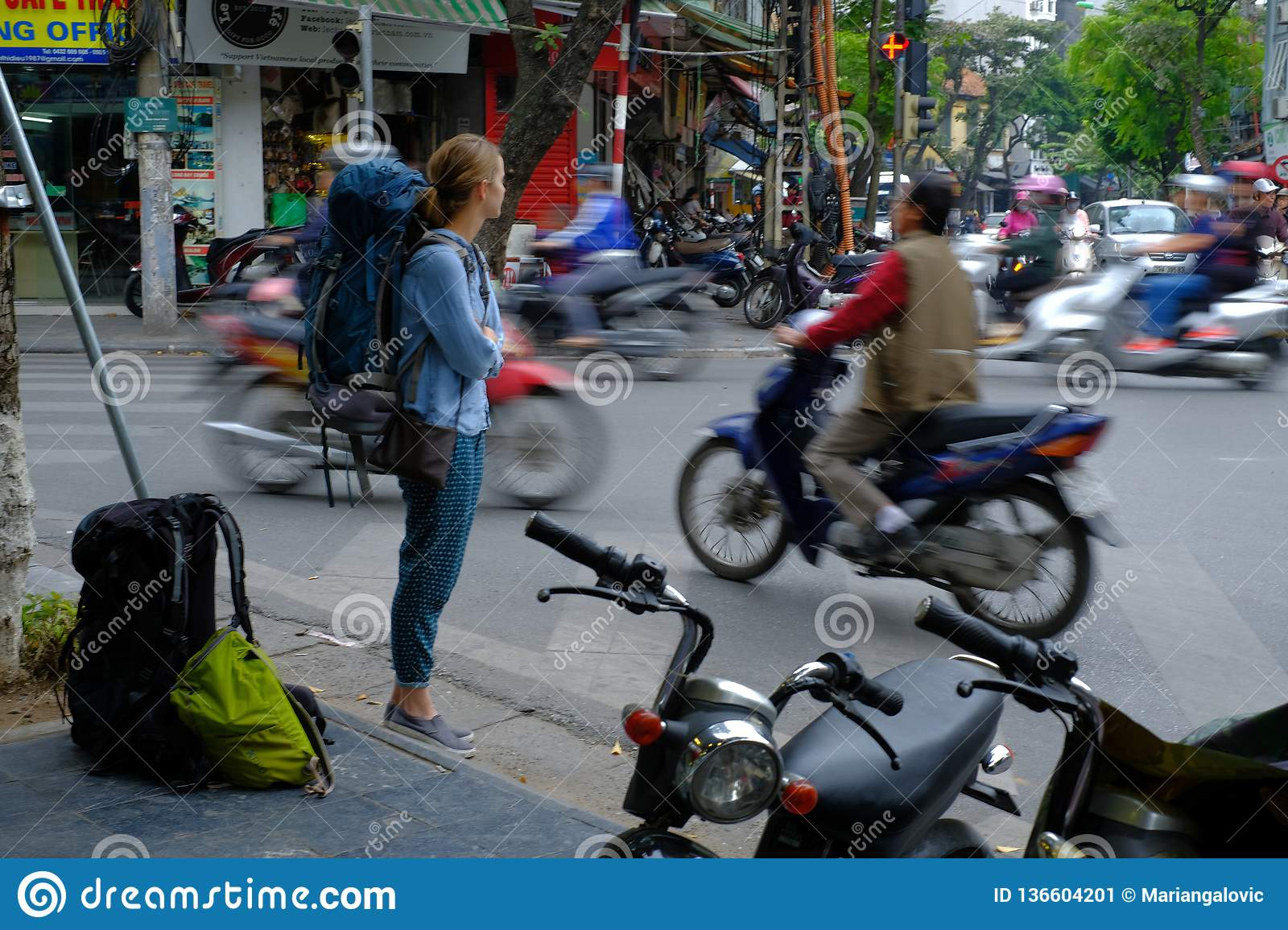 Hanoi / Vietnam, 05/11/2017: Backpacker watching busy hectic traffic with passing cars and motorbikes on a Hanoi street