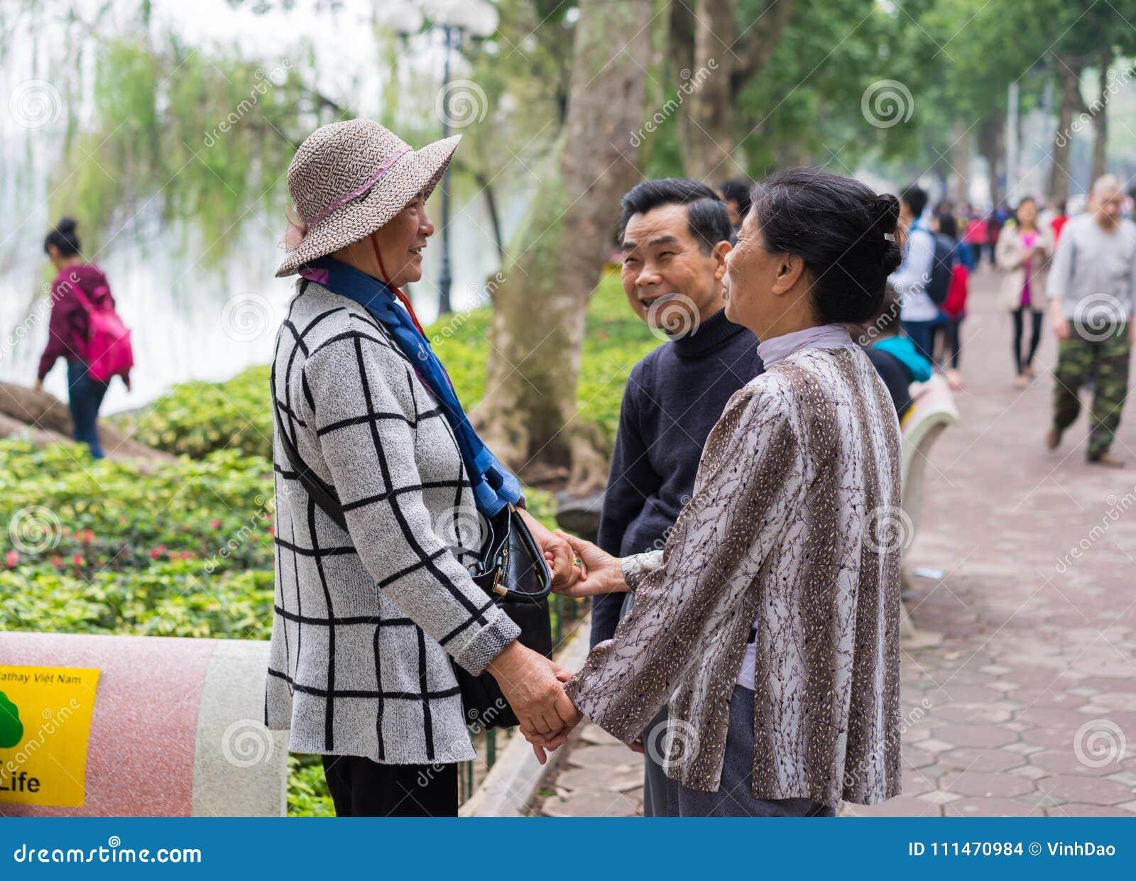 Hanoi, Vietnam - 15 de marzo de 2015: Un par que ve feliz a su amigo en el lago Hoan Kiem, distrito de Hoan Kiem Las mujeres que
