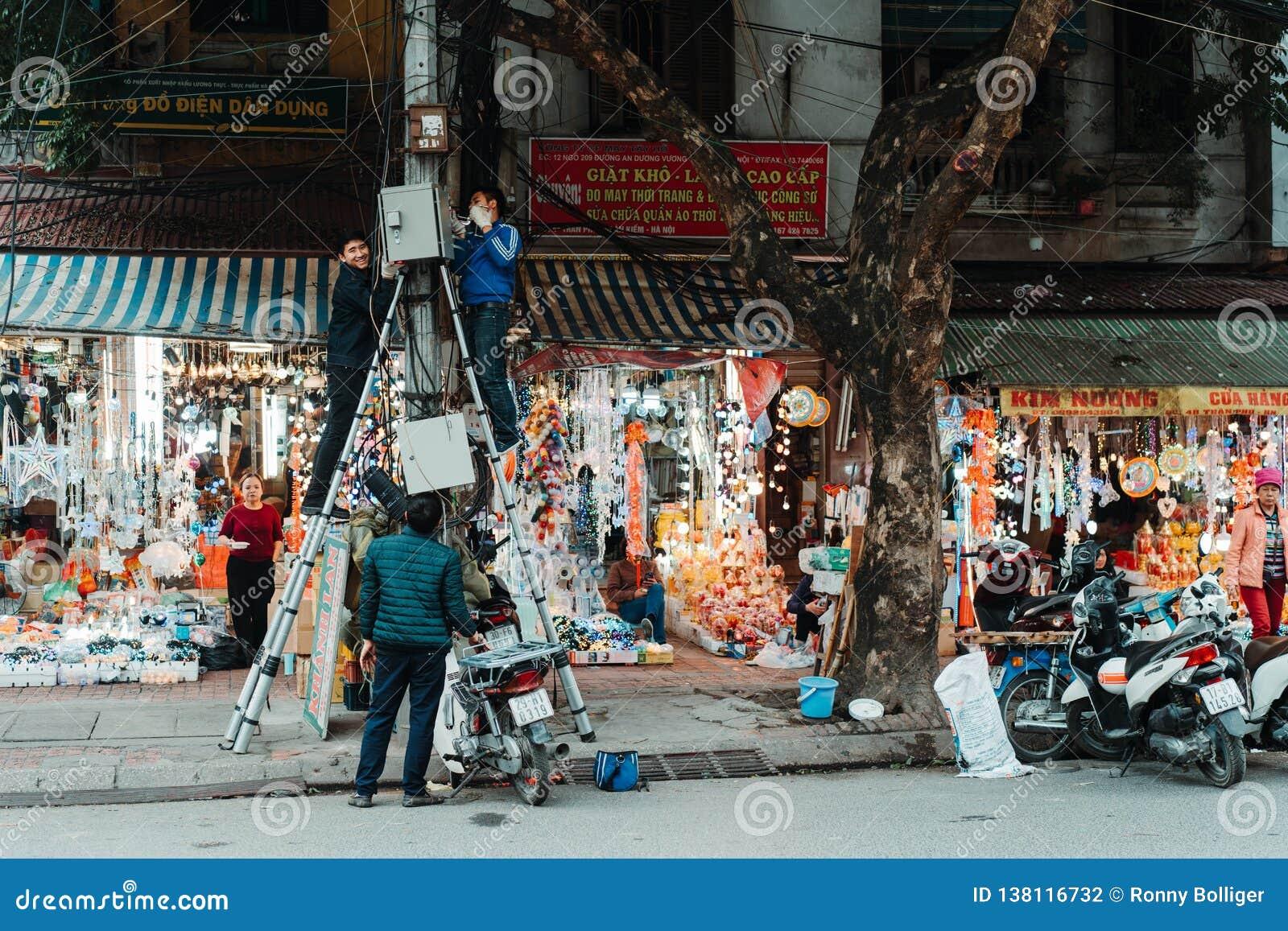 Hanoi, Vietnam, 12 20 18: Het leven in de straat in Hanoi De elektricien probeert om één of ander probleem met de elektriciteit t