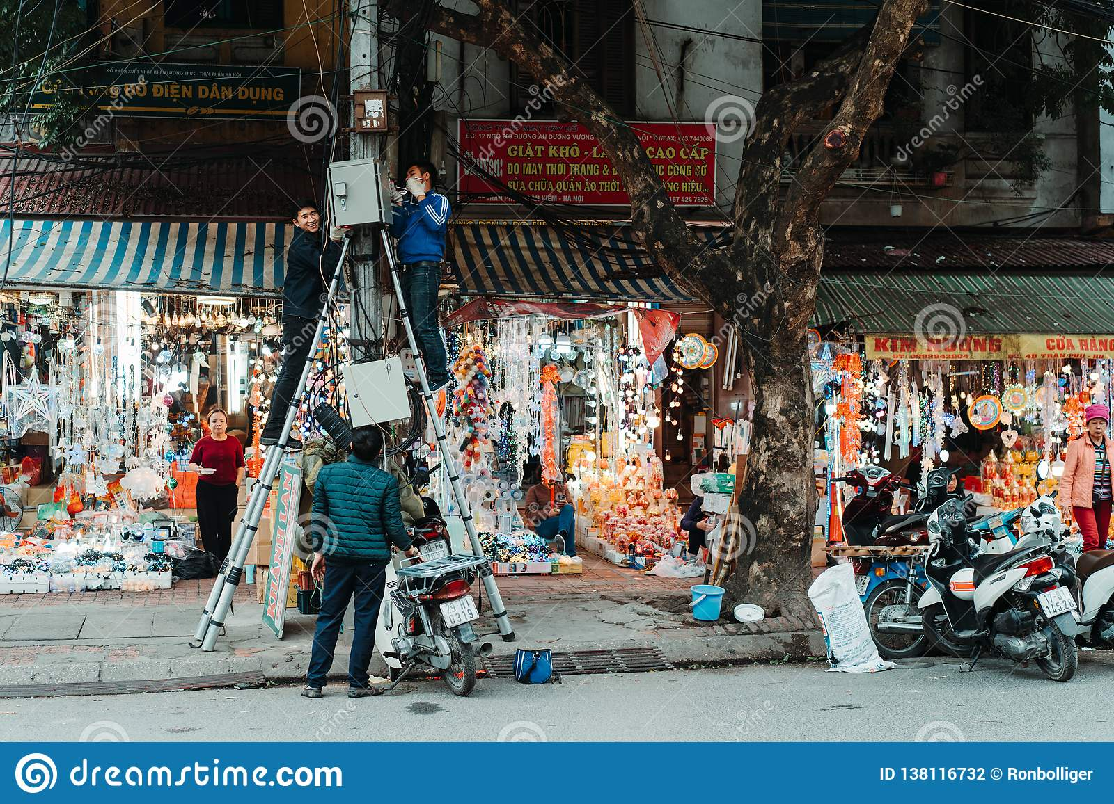 Hanoi, Vietnam, 12.20.18: Life in the street in Hanoi. Electrician try to fix some problem with the electricity .