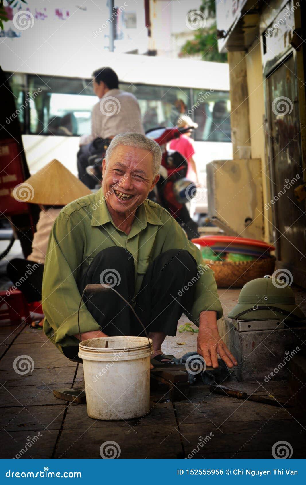 Hanoi, Vietnam - luglio 05,2019: Un uomo anziano dell affilatrice sta lavorando nella via con il fronte felice