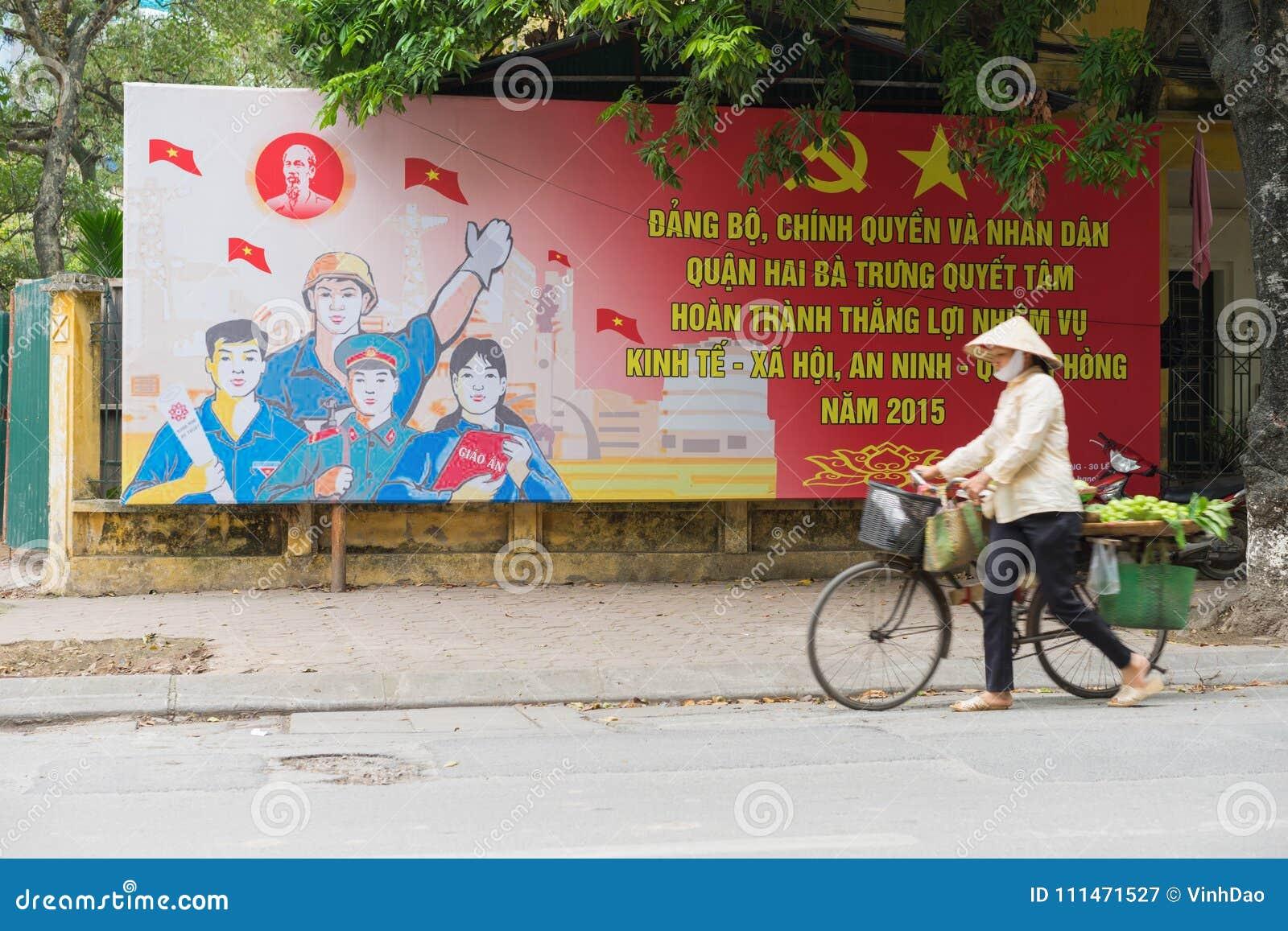 Hanoi, Vietnam - 29. März 2015: Ein gehender Durchlauf des Verkäufers eine kommunistische Propaganda herein zu Straße Hien Thanh