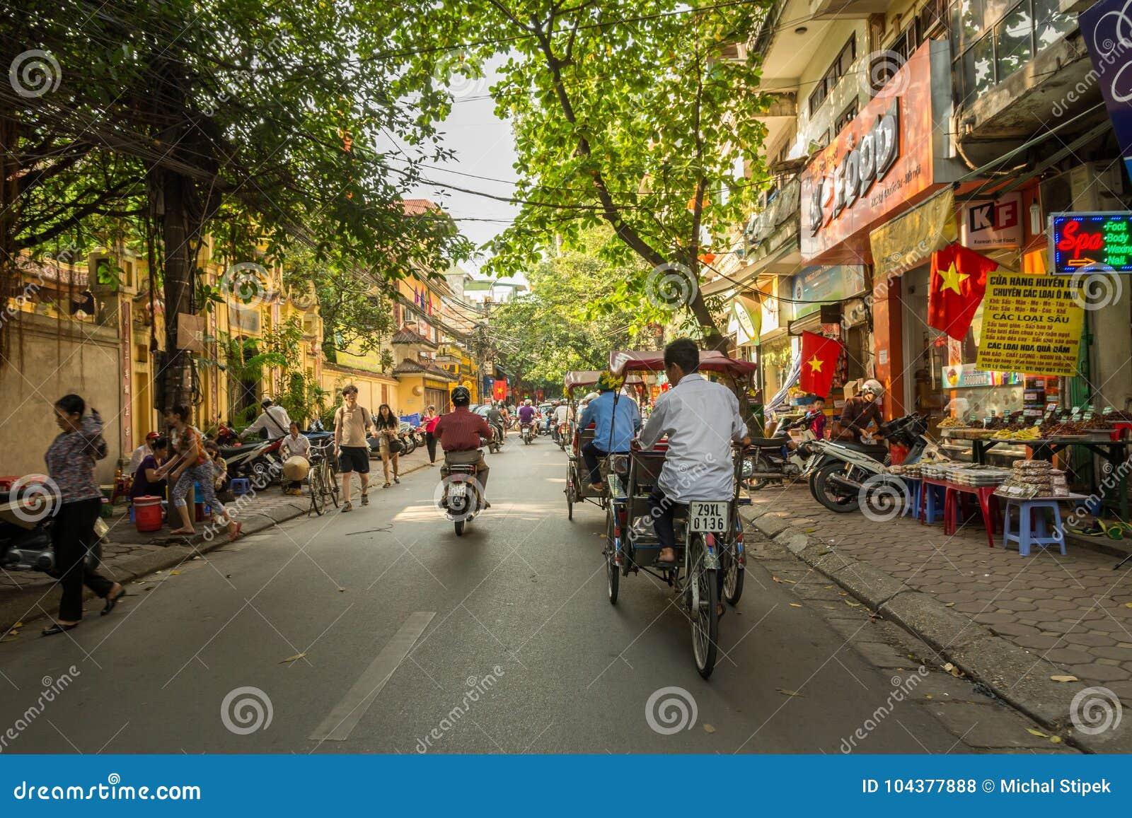 Rickshaw driver on busy street in Hanoi, Vietnam