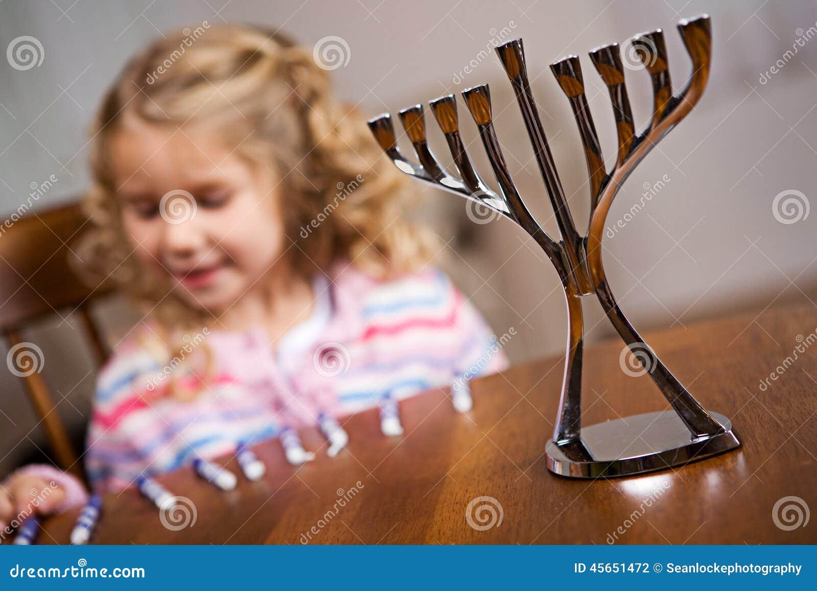 Hanukkah: Foco no Hanukkah Menorah com da menina parte traseira dentro