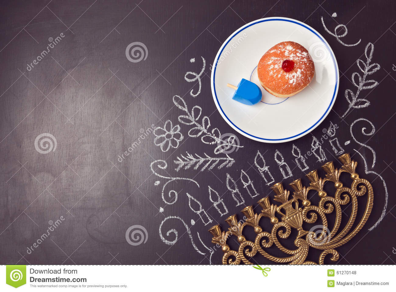 Hanukkah holiday background with menorah and sufganiyot over chalkboard. View from above