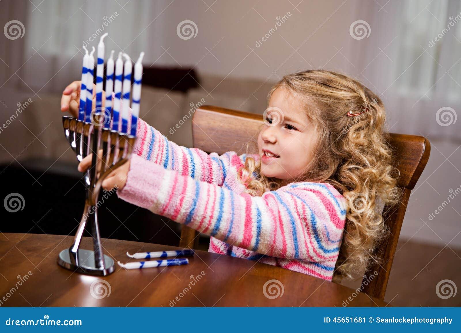 Hanukkah: Menina que põe velas em Menorah