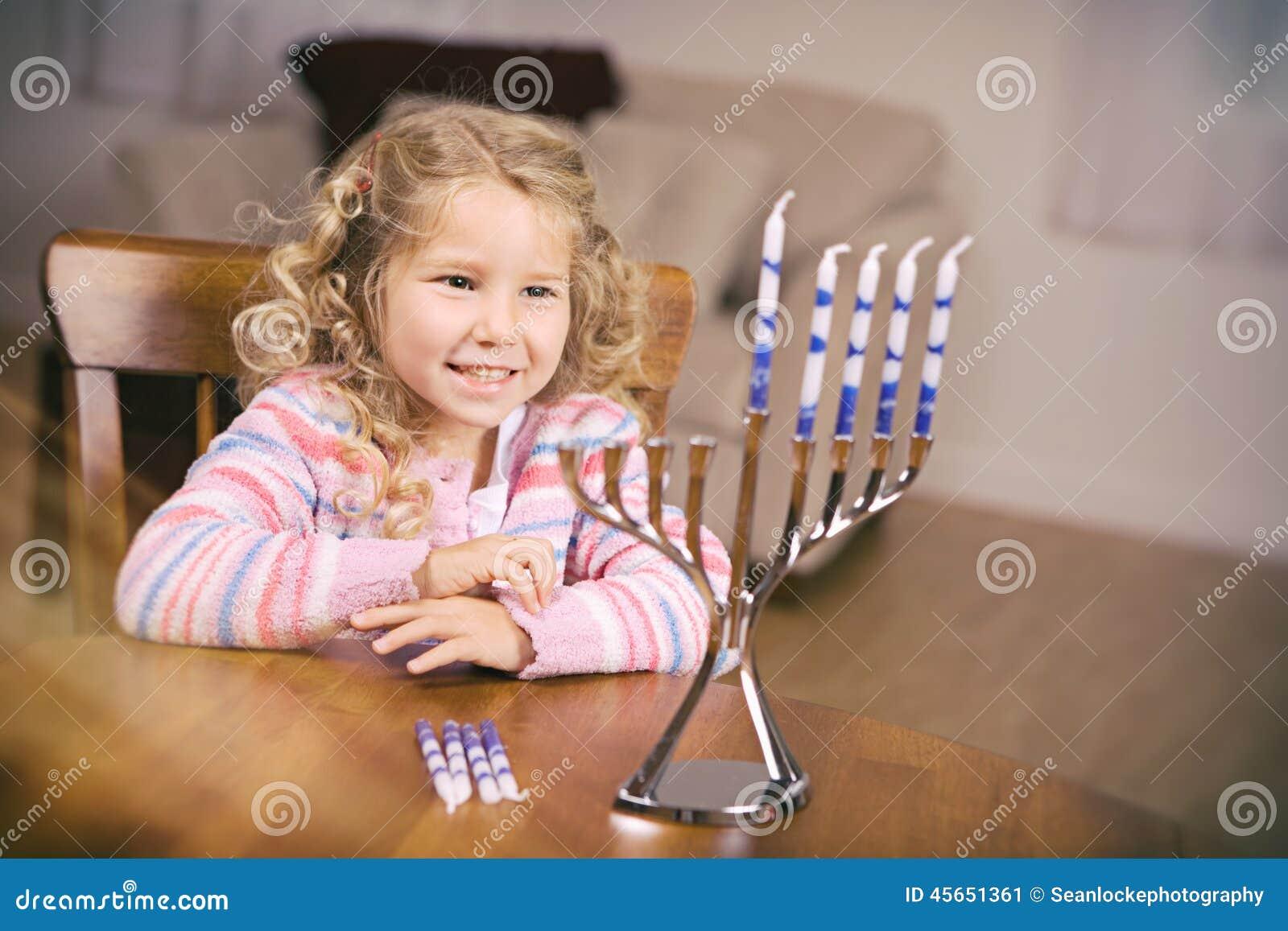 Hanukkah: Menina que senta-se na tabela pronta para iluminar velas