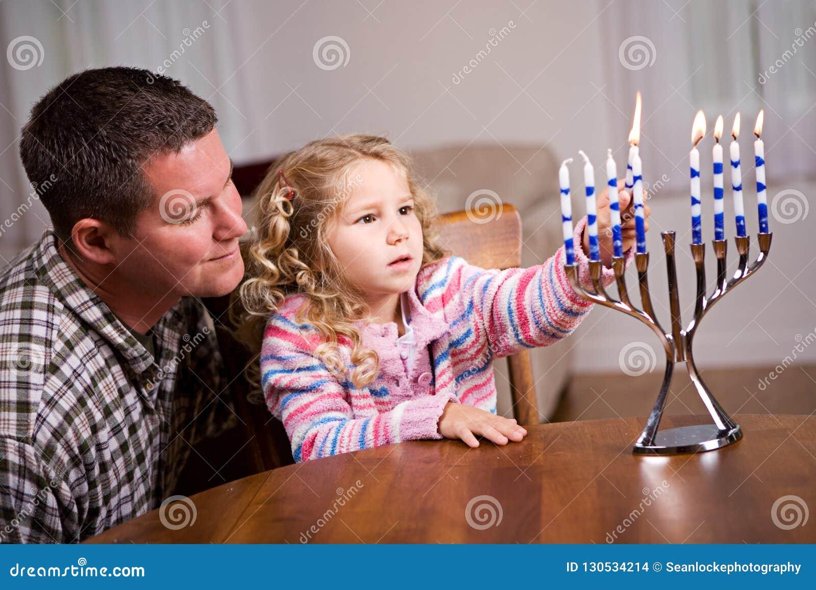 Hanukkah: Velas do Hanukkah da luz da menina e do pai junto