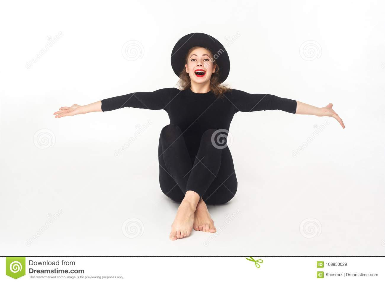 Happiness beautiful woman in hat, sitting on floor.