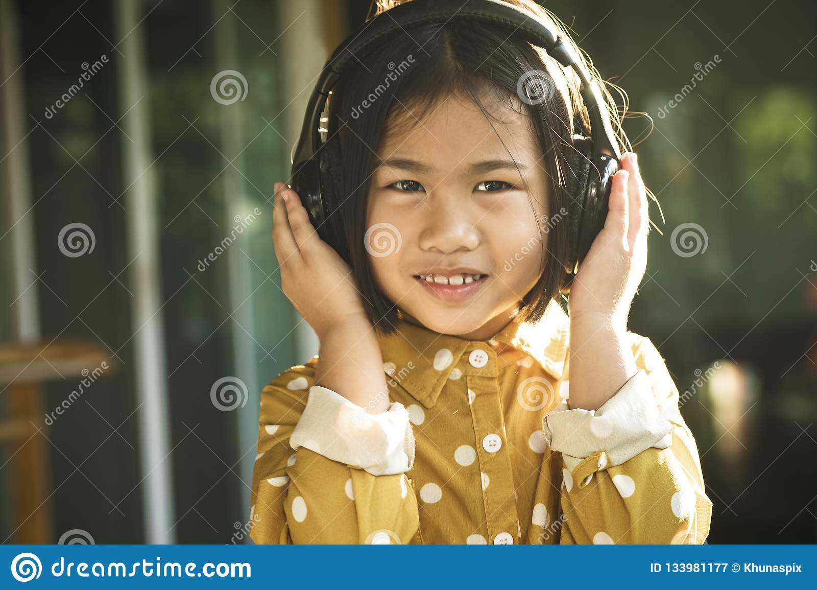 Happiness face of asian children listening music in head phone