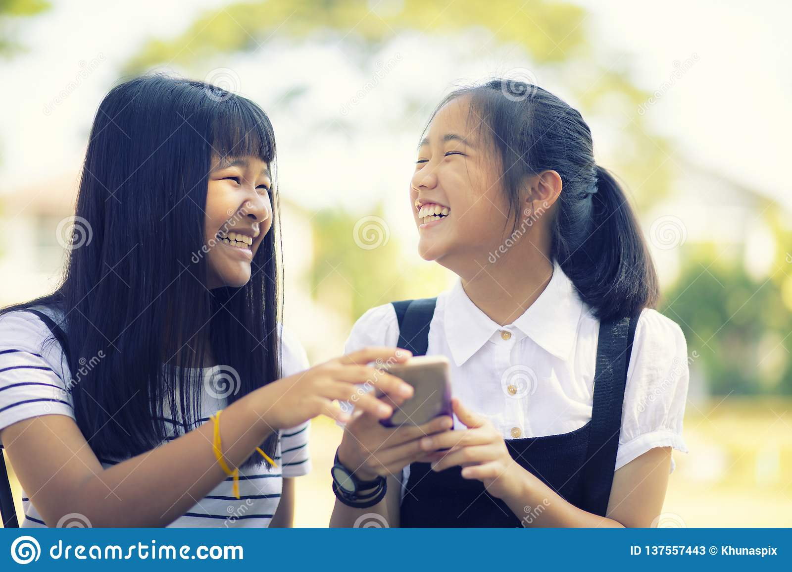 Happiness face of asian teenager holding smart phone in hand with toothy smiling face
