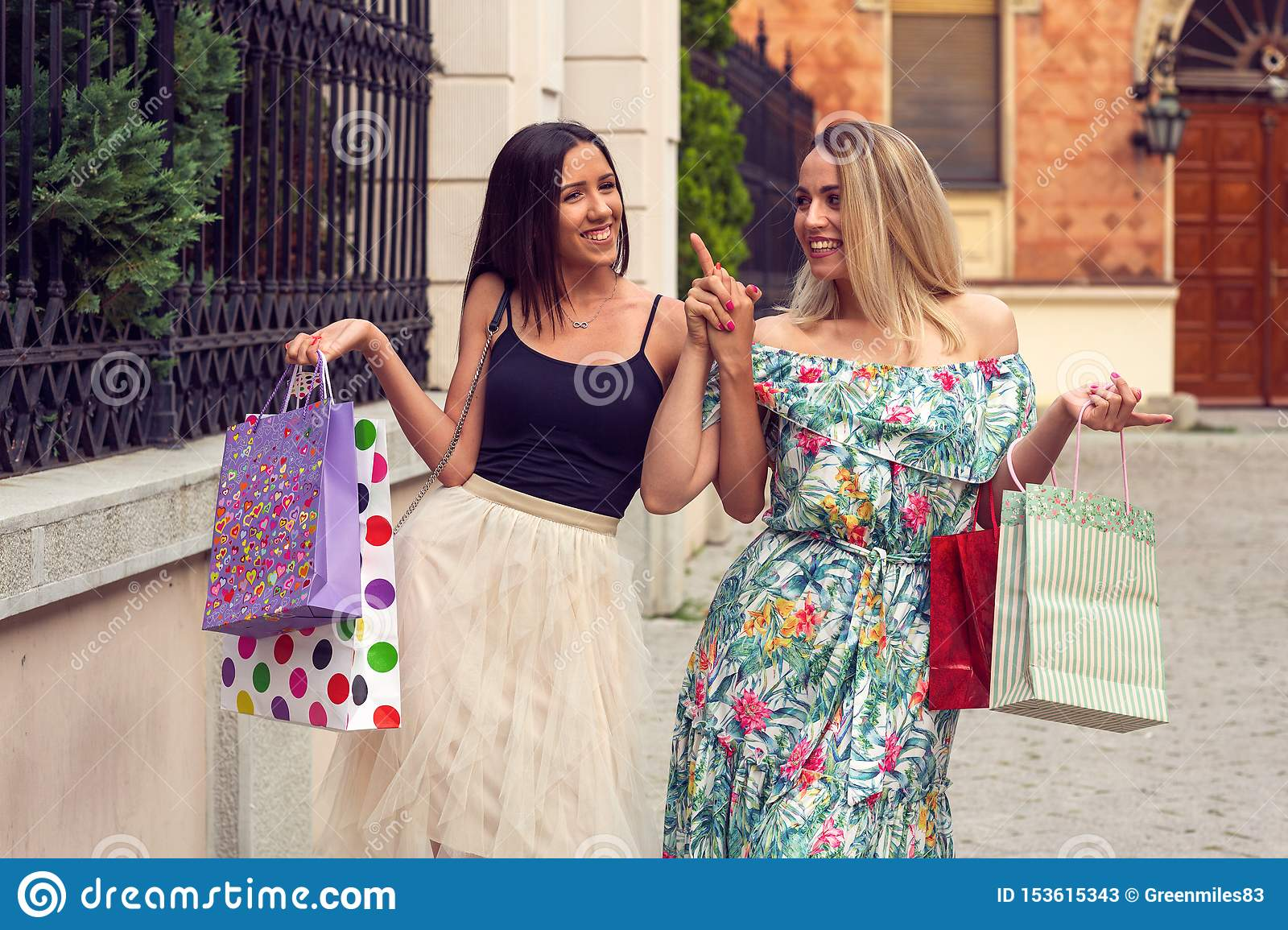 Happiness, friends, sale and fun concept-smiling girlfriends with shopping bags